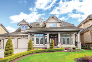 Beautiful front of House with 2 car garage manicured bushes in spirals